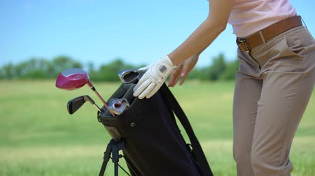tomar : Female golfer putting sports bag on course, taking iron club to play game, hobby Stock Footage