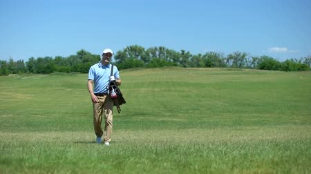 regulamin : Skilled male golf trainer walking on course with clubs bag recreational activity