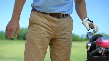 cursos : Professional male golf player taking iron club, standing in basic ball position