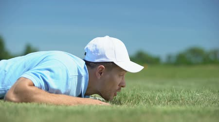 adam : Cunning male golf player blowing ball in hole at course, successful shot, fun