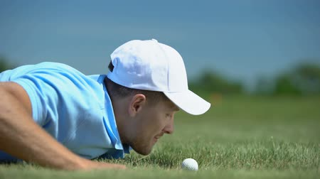 golfbaan : Tricky man blowing golf ball in hole, agility and cunning success strategy hobby