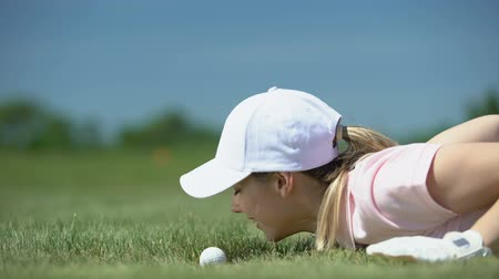 schemat : Cunning woman hitting golf ball in hole with finger, having fun during game