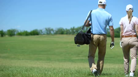 elite : Couple of male and female golfers walking on course with clubs bag, lesson
