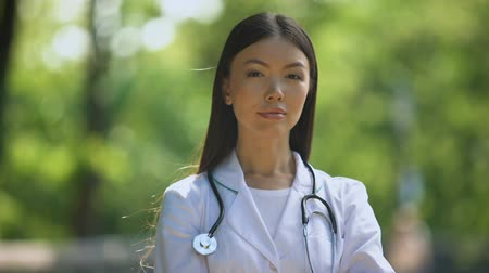 rehabilitasyon : Confident nurse looking into camera in hospital park, medical profession, health