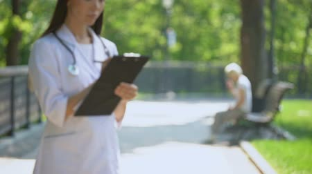 вред : Medical worker filling medical data in park, woman smoking on background