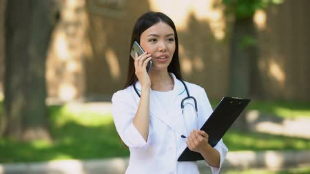 informando : Beautiful nurse talking smartphone with patient at rehabilitation center park