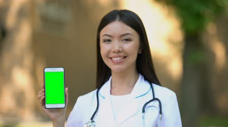 gadżet : Smiling female doctor showing smartphone with green screen at camera, health