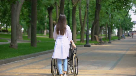 chirurgia : Female nurse walking in park with disabled patient, rehabilitation center Wideo