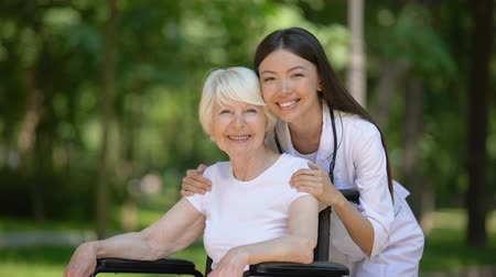 rehabilitasyon : Smiling female nurse hugging disabled elderly woman and looking at camera