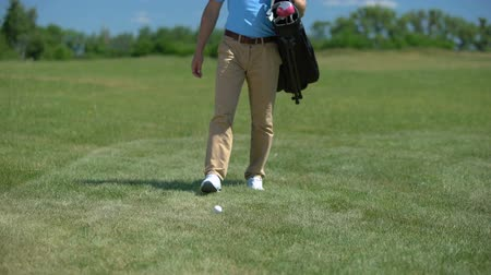 хит : Man golfer putting sport equipment bag on green, taking club and ready to play