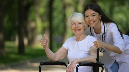 kciuk : Nurse and elderly woman in wheelchair smiling at camera and showing thumbs-up