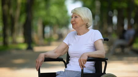 bizakodó : Happy elderly female in wheelchair enjoying sunny day in park, rehabilitation