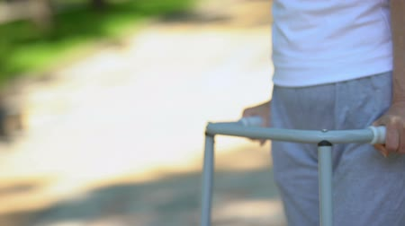 diz : Senior woman moving outdoors with walking frame, knee joint replacement surgery Stok Video