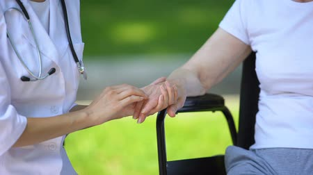 assistência : Female therapist holding hand of disabled elderly woman in wheelchair, outdoors
