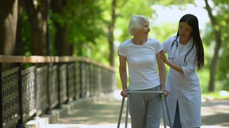 pacjent : Female doctor helping elderly woman with walking frame, hospital park, outdoors