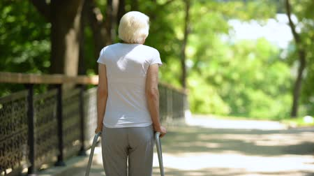pacjent : Elderly woman moving with walking frame at rehabilitation center park, back view