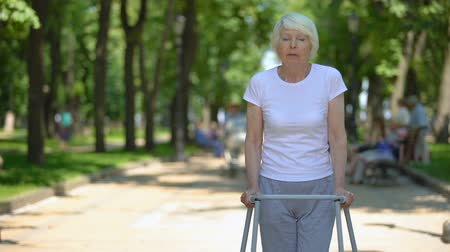 pacjent : Upset old woman moving outdoors with walking frame, rehabilitation after trauma