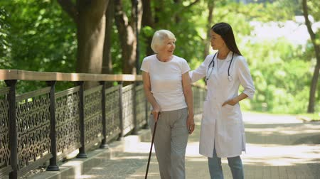 колено : Doctor walking in park with elderly female patient with cane, rehabilitation Стоковые видеозаписи