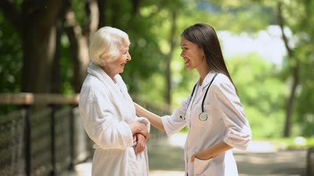 beszélő : Smiling nurse talking with elderly woman in bathrobe at sanatoria park, relax