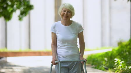 důchodce : Cheerful senior woman with walking frame looking at camera outdoors, rehab