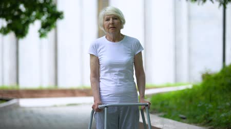 chirurgia : Sad old female with walking frame at sunny hospital park, ineffective treatment