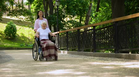 důchodce : Granddaughter pushing old woman in wheelchair hospital garden, support and care