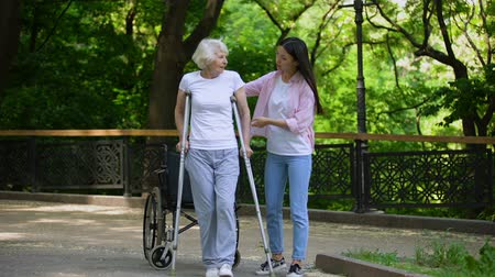 kule : Young woman helping old lady walking on crutches, hip fracture rehabilitation