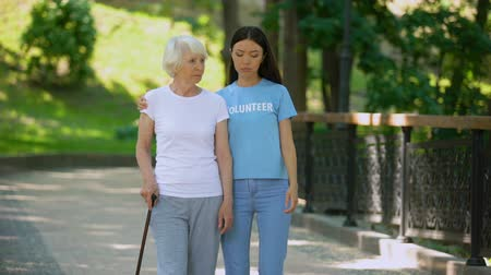 důchodce : Depressed mature woman with walking stick and female volunteer in garden, rehab Dostupné videozáznamy