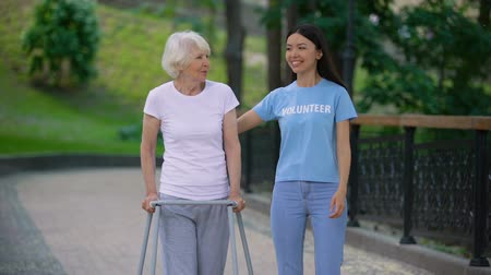 olgun : Caring young woman supporting old lady with walking frame, social volunteering Stok Video