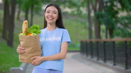 пожертвование : Cheerful female volunteer holding grocery bag outdoors smiling camera, donation