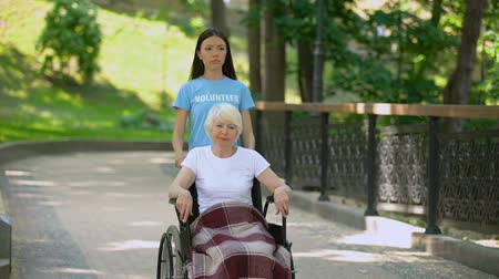 пенсионер : Young woman pushing upset old lady wheelchair, sickness depression, medicine
