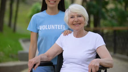 nursing : Happy mature woman in wheelchair and young volunteer looking camera, charity Stock Footage