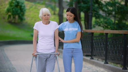 Female volunteer supporting sick old woman walking frame, rehab difficulties