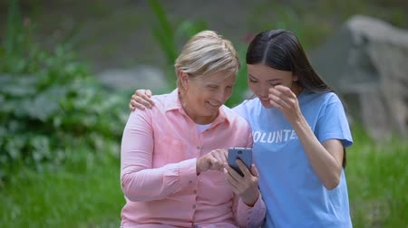 tür : Mature woman and young volunteer looking smartphone photos together, assistance