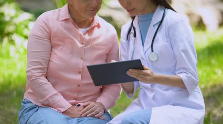 tür : Young doctor showing images on tablet discussing diagnosis aged female patient
