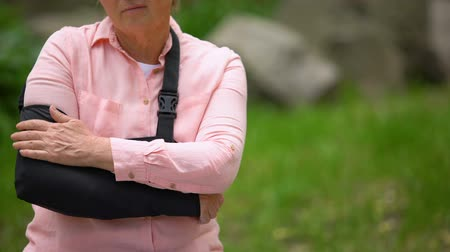 dişli : Injured mature woman arm sling suffering pain sitting outdoors, elbow fracture