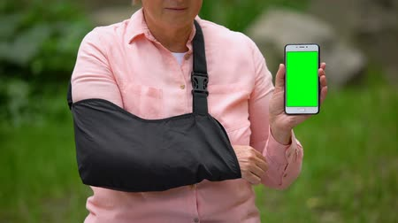 dişli : Senior woman wearing shoulder immobilizing sling showing smartphone green screen