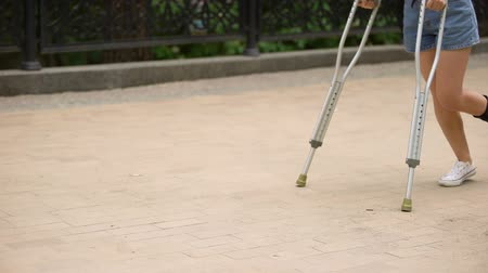 발목 : Woman with injured ankle walking on crutches outdoors, leg strain, fracture