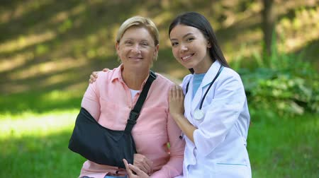 ortopedia : Happy female doctor hugging aged lady in shoulder immobilizing sling, health
