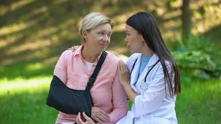 pacjent : Professional podiatrist comforting injured old lady arm sling, recovery advise Wideo