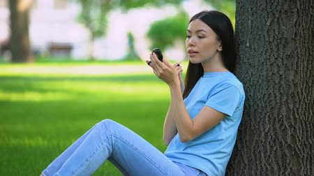 ponta : Pretty asian woman applying lip gloss smiling small mirror sitting park, beauty Stock Footage