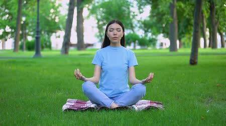 дзен : Attractive young lady meditating in park sitting lotus pose, relaxing outdoors