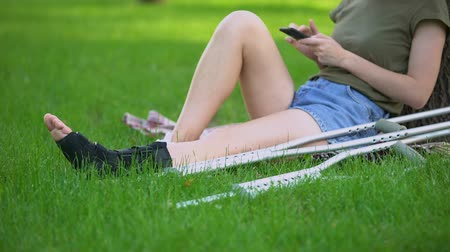 醫療保健 : Woman in ankle brace sitting park with crutches scrolling smartphone, fracture