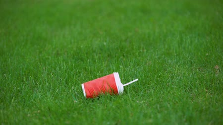 esquerda : Empty paper cup falling on grass, food waste recycling, environmental protection