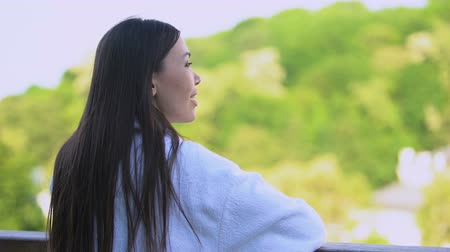 отель : Smiling young lady white bathrobe looking outdoors relaxing spa center balcony