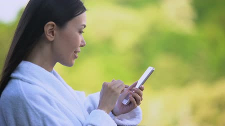 отель : Joyful woman in white bathrobe scrolling smartphone photos, vacation leisure