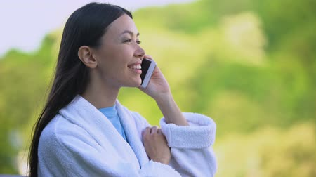 отель : Happy attractive female in bathrobe talking on phone, luxury resort vacation