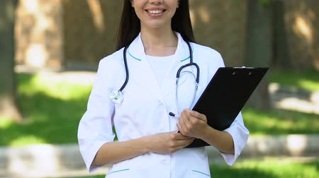 konsultant : Highly qualified doctor with folder and stethoscope smiling standing outdoor