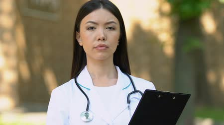 konsultant : Worried doctor with medical records looking into camera standing outdoor