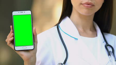 registrace : Physician holding green screen smartphone in hand, online registration to doctor
